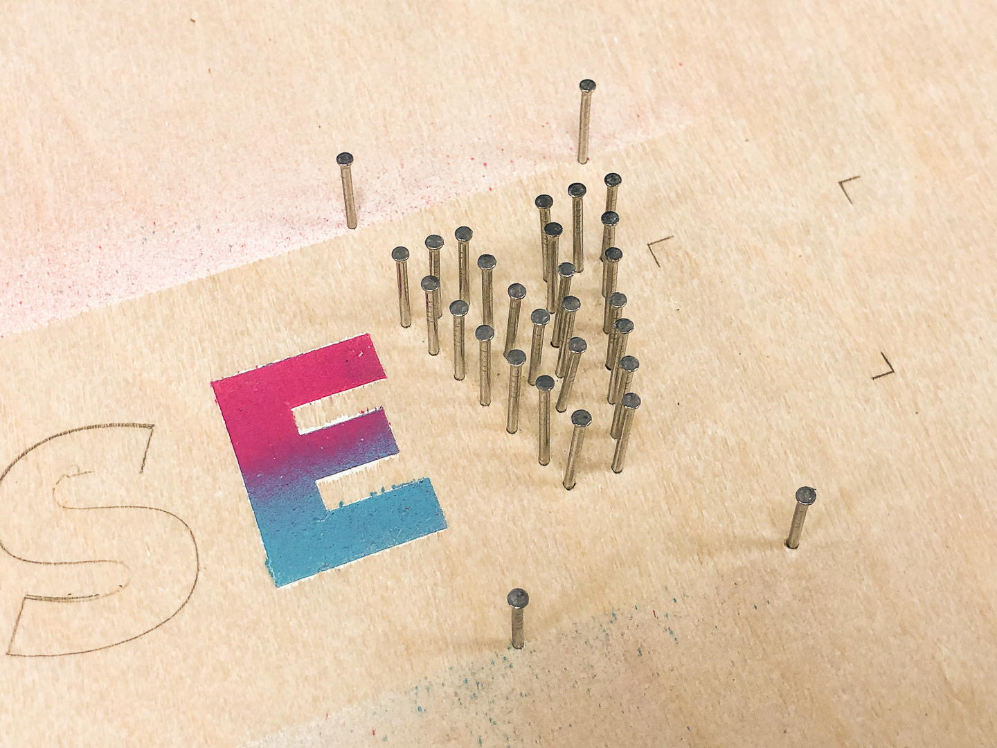 Panel pins in shape of letter V on plywood